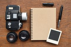 notebook with pen, photo frames and camera - stock photo