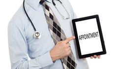 Doctor holding tablet - Appointment - stock photo