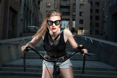 Woman in sunglasses on the bike. Stock Photos