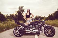 Beautiful young woman posing with a motorcycle Stock Photos