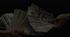 Two hands fan large stacks of hundred dollar bills towards the camera at 72 fps Stock Footage