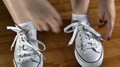 Young Woman Untying The Shoelaces Of Her Sport Shoes, High Angle Stock Footage