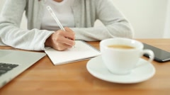 Woman writing on notebook on her desk Stock Footage