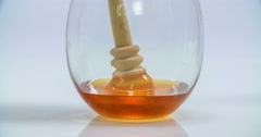 Slowly lifting up a wooden honey stick in a glass Stock Footage