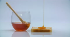 Pouring some honey on a piece of toast Stock Footage