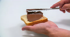 Spreading out some nutella on a piece of toast Stock Footage