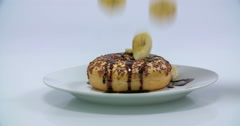 A few pieces of banana fall on a chocolate doughnut Stock Footage