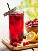 Ice cold drink glass with raspberry and lemon cocktail . - stock photo