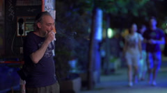Smoker standing next to a phone booth at night in city street Stock Footage