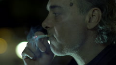 Smoker with a cigarette evening illuminated by the headlights of cars Stock Footage