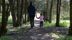 Walking mother and beautiful little daughter at the shady walkway in the park Stock Footage
