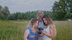 Female photographer showing photos for adult couple during fashion photo shoot - stock footage