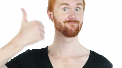 Portrait of happy man showing thumbs up while standing against white background Stock Footage