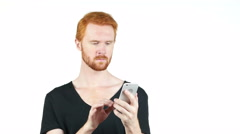 Young red hair man holding mobile smartphone using app texting sms message Stock Footage