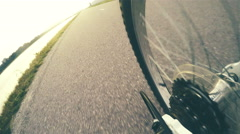 4k bicycle rear wheel footage: a bicyclist rides along the asphalted road Stock Footage