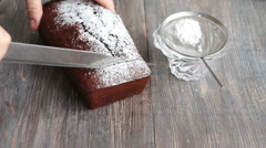 Cutting chocolate and cherry cake frosted with sugar powder Stock Footage