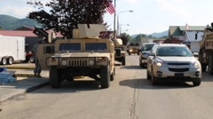 Cars Pass National Guard Humvee in Town Stock Footage