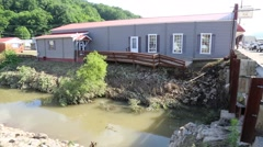 Flood Damaged House with Deck Falling into River Stock Footage
