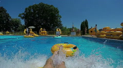 Personal view of man going down the waterslide in to the pool of water park Stock Footage