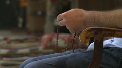 Man sitting in a chair playing with beads in istanbul Stock Footage