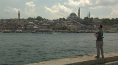 A man with a fishing rod at marmara with most in background in istanbul Stock Footage