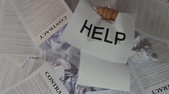 Hand with help word emerges from the pile of papers. Stock Footage