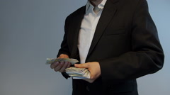 Businessman takes out money counts it and hides into his pocket. Stock Footage
