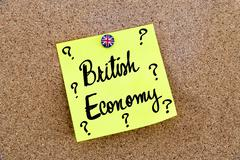 Yellow paper note pinned on cork board with Great Britain flag thumbtack, wri - stock photo