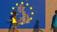 People walking by a tattered EU poster on a brick wall Stock Footage