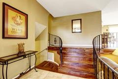 Large bright hallway interior design. Nice basement staircase with metal rail Stock Photos