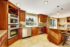 Luxury kitchen with tile floor, stained cabinets and granite counter top - stock photo