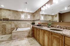 Luxury bathroom interior with tile floor. Bath tub with brown granite tile tr - stock photo