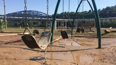 Teetering Swing Seat over Flood Destroyed Playground Stock Footage