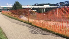 Closeup of Silt Fence with Trucks and Bridge in Background Stock Footage