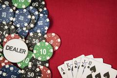 Gambling chips, dealer chip and card for poker on red felt background - stock photo
