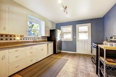 Kitchen interior with white cabinets, tile floor and bright navy walls - stock photo