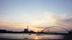 Sunset behind industry and bridge across busy river, 4K time lapse Stock Footage