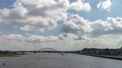 Fast moving clouds above river with views of a traffic bridge, 4K time lapse Stock Footage