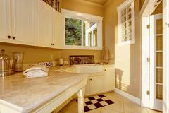 Bright kitchen room area with white cabinets, granite counter top and tile fl - stock photo