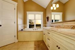 Cozy bathroom interior with old white cabinets, tile floor and vaulted ceilin Stock Photos