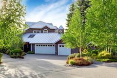 Modern large house exterior with curb appeal. View of garage and concrete flo - stock photo