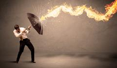 Business man defending himself from a fire arrow with an umbrella - stock photo