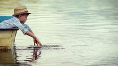 A wee boy sprinkles water all around sitting in the wooden boat moored on lake Stock Footage