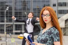 Redhair woman posing on jumping businessman background Stock Photos