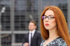 Redhair woman posing on jumping businessman background - stock photo