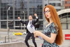 Red-haired businesswoman and businessman on background Stock Photos