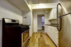 White old kitchen with stainless steal appliances and hardwood floor Stock Photos