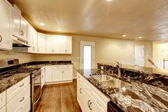 Kitchen room with white appliances, granite counter top, kitchen island and h - stock photo