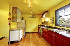 Kitchen room interior with yellow walls and red cabinets. Countryside house Stock Photos