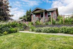 Big farmhouse with beautiful flowerbed, concrete walkway and attached back ya - stock photo